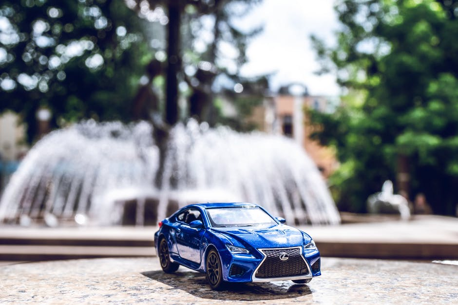 blue car with fountain in background