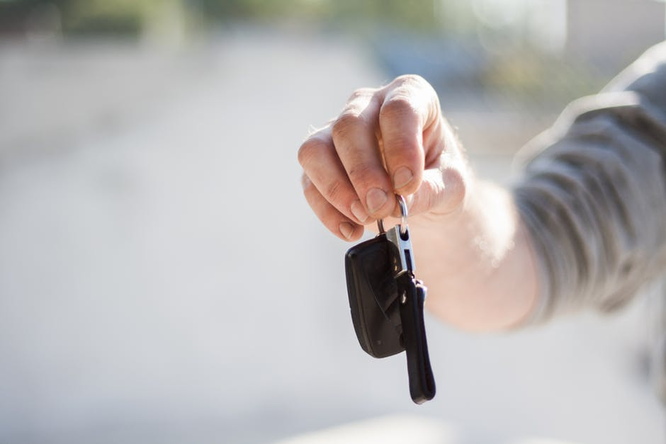 person holding keys to sell a car