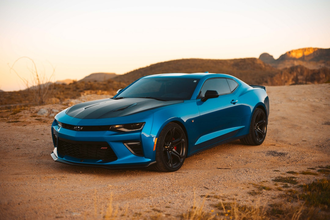 blue Chevrolet on dirt road