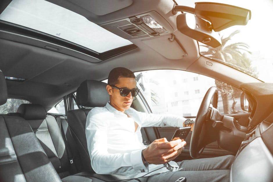 Man Using Smartphone on His Car